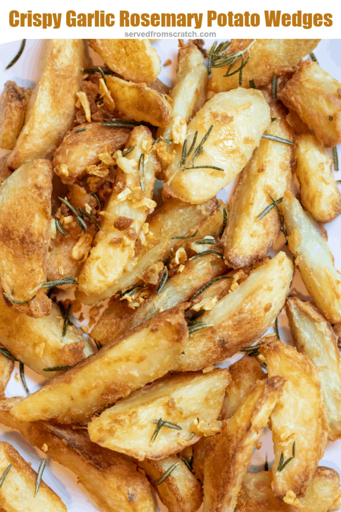 a plate of baked potato wedges topped with rosemary and garlic with Pinterest pin text.