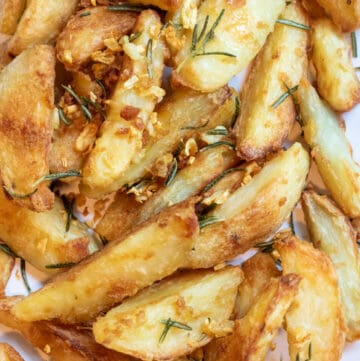 a plate of baked potato wedges topped with rosemary and garlic.
