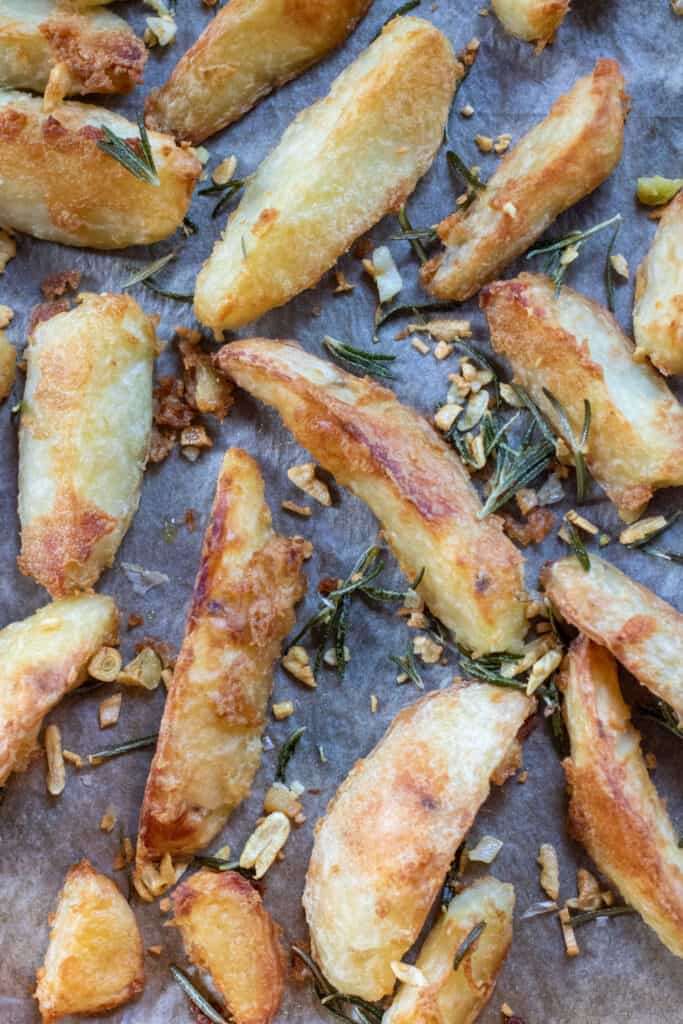 baked potato wedges on a baking sheet topped with garlic and rosemary