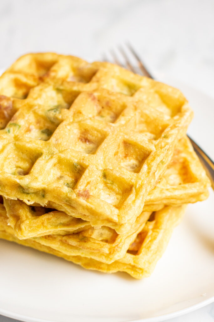 stacked egg waffles on a plate with a fork