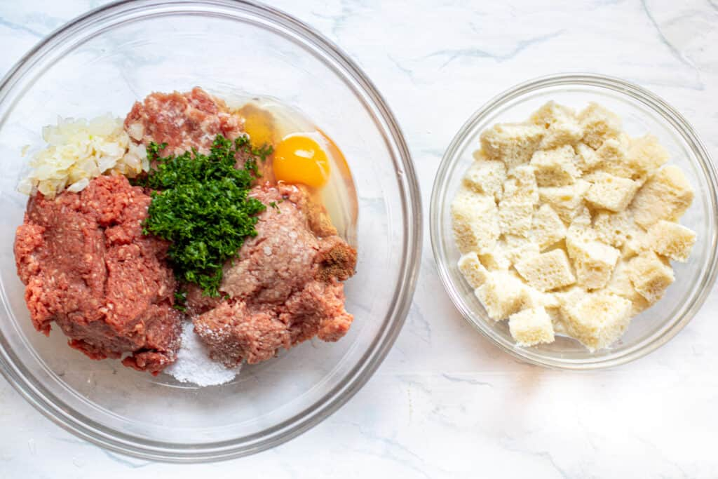 a bowl of meats, parsley, egg, onion, spices next to a bowl of soft bread crumbs