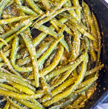 cooked green beans in a pan coated with mustard.