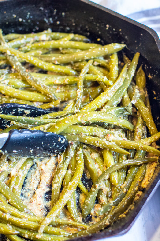 cooked green beans in a pan coated with mustard with tongs