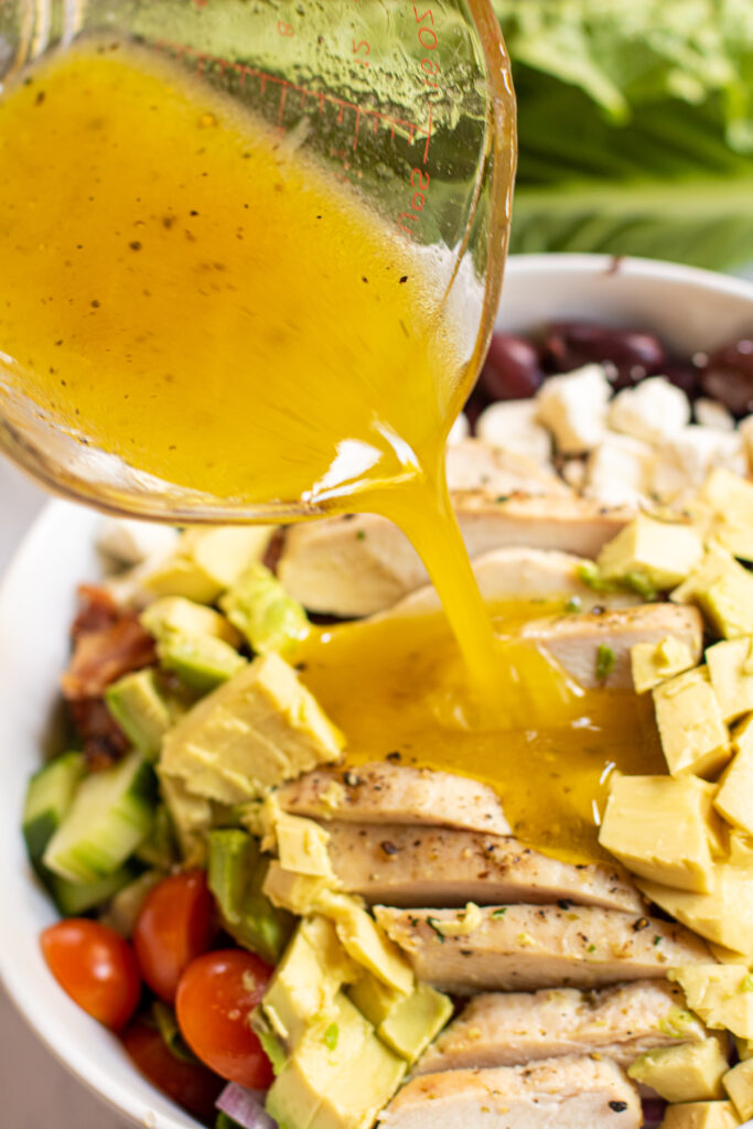 lemon vinaigrette being poured on a salad with chicken.