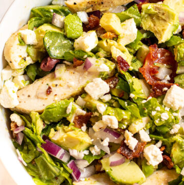 bowl of salad with chicken, feta, tomatoes.
