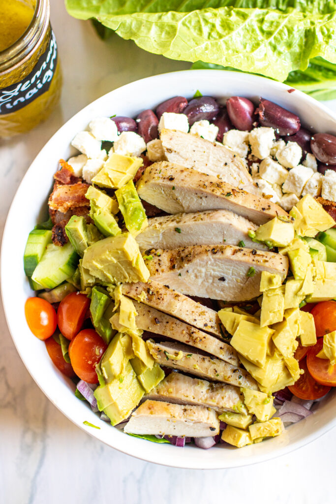 an over head of salad with chicken avocado, feta, olives, cucumbers, and tomatoes.