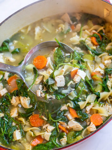 a pot of veggie noodle soup with spinach with ladle.