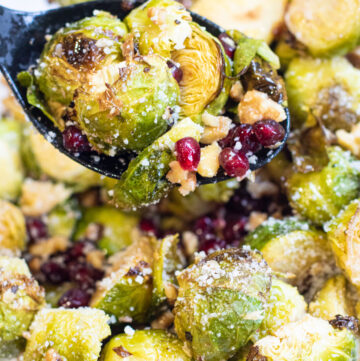a spoon with roasted brussels, walnuts, and pomegranates