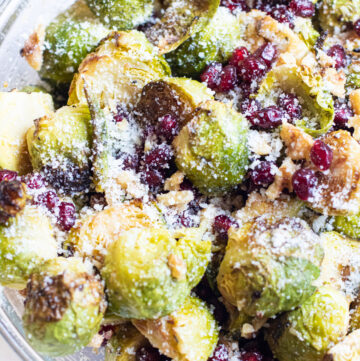 bowl of brussels sprouts and pomegranates topped with cheese.