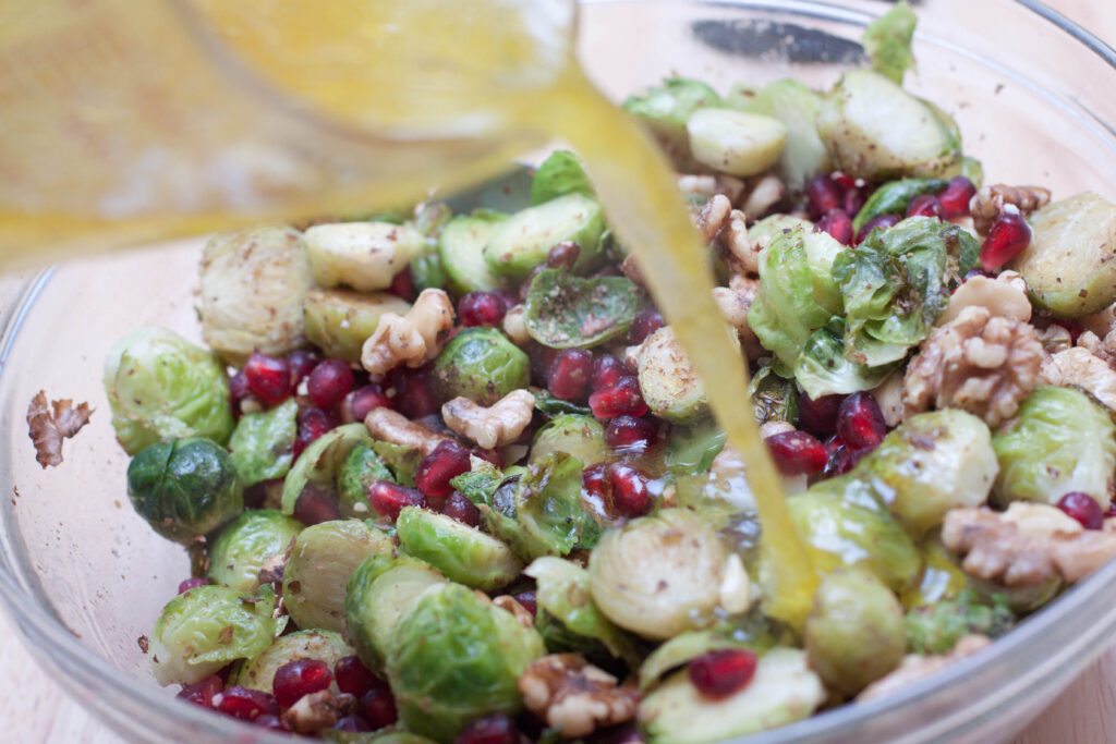 a bowl of brussels sprouts salad with pomegranates and cheese with vinaigrette being poured in