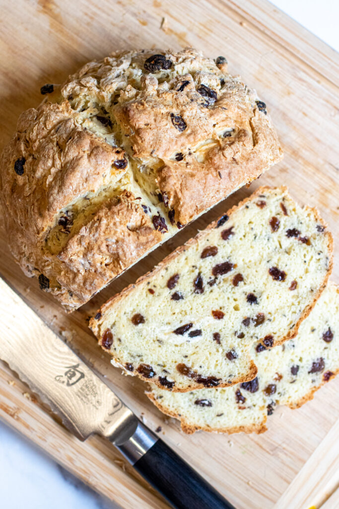 baked bread with raisins sliced on cutting board