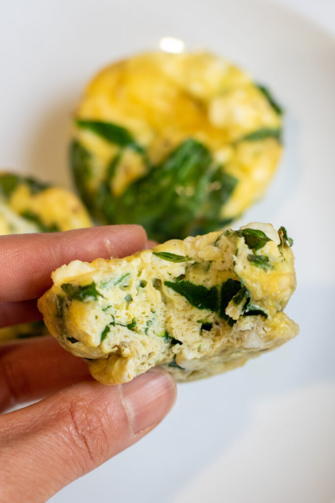 an egg cup with spinach with a bite taken out