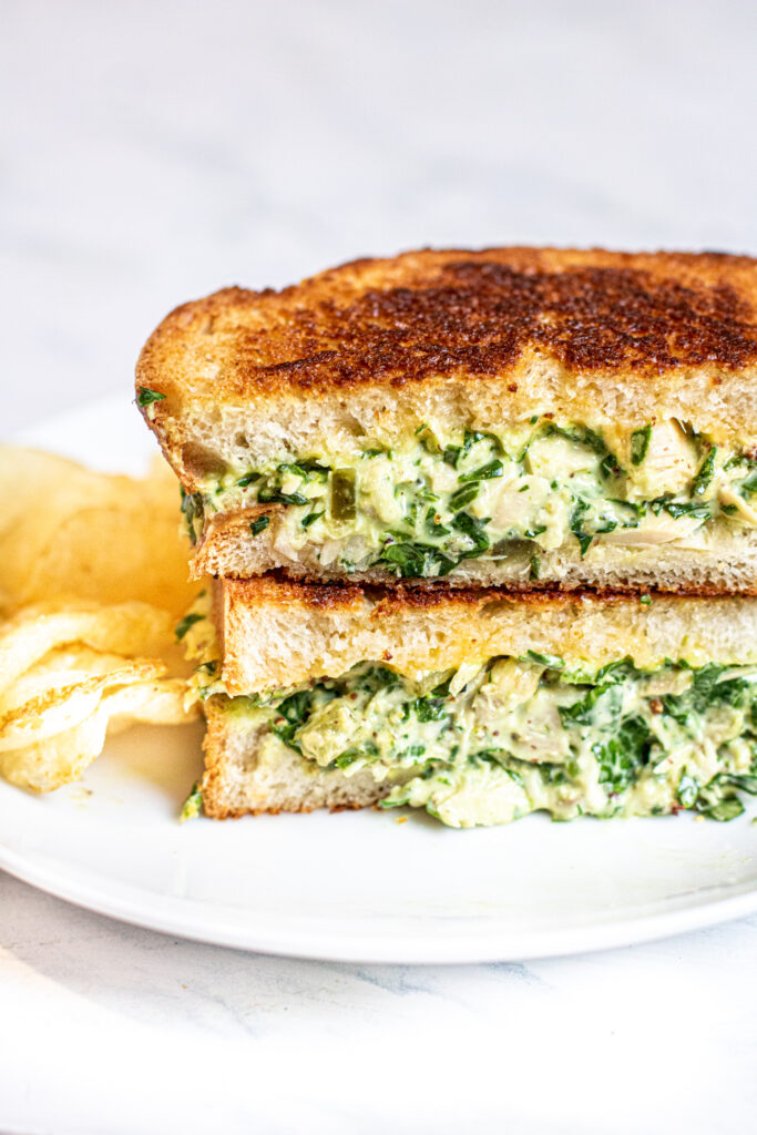stacked tuna melt with spinach on a plate with chips.