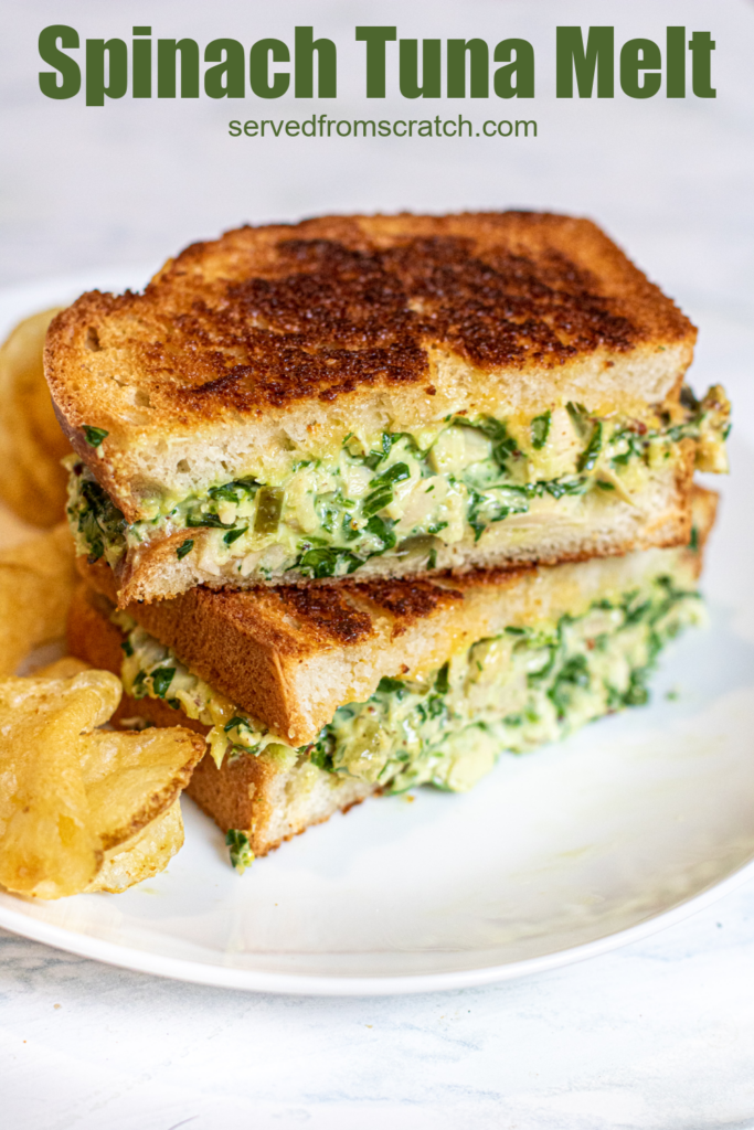 stacked tuna melt with spinach on a plate with chips