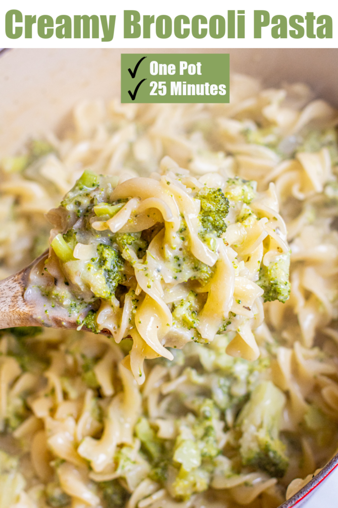 a wooden spoon holding some creamy pasta and broccoli
