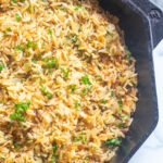 a cast iron with cooked rice pilaf and parsley.