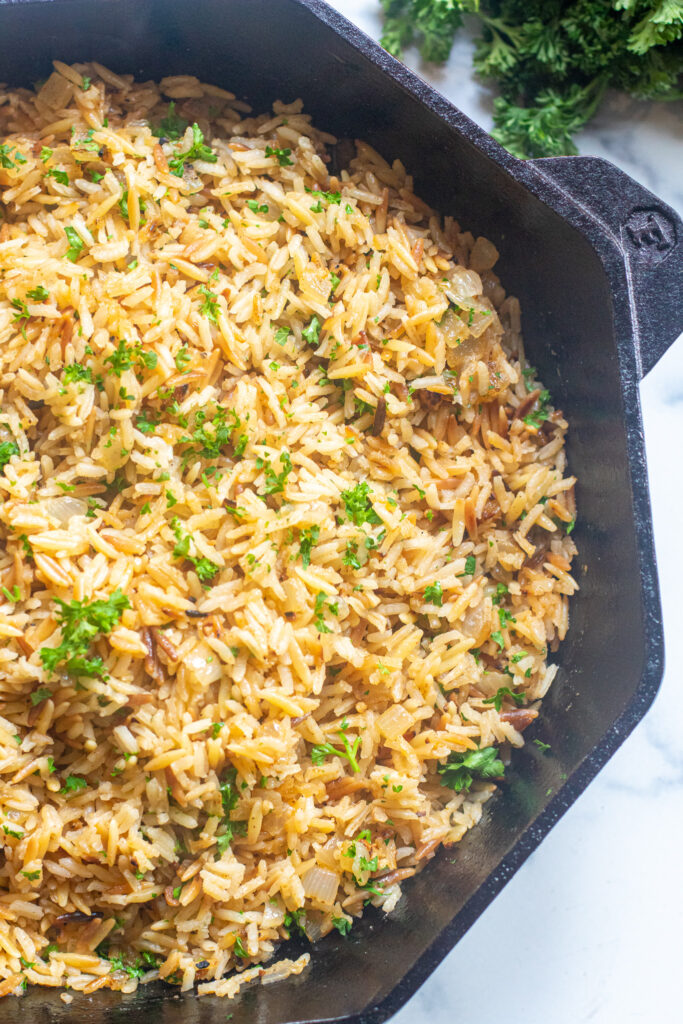 a cast iron with cooked rice pilaf and parsley