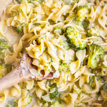 overhead of a wooden spoon in a creamy pot of pasta with broccoli