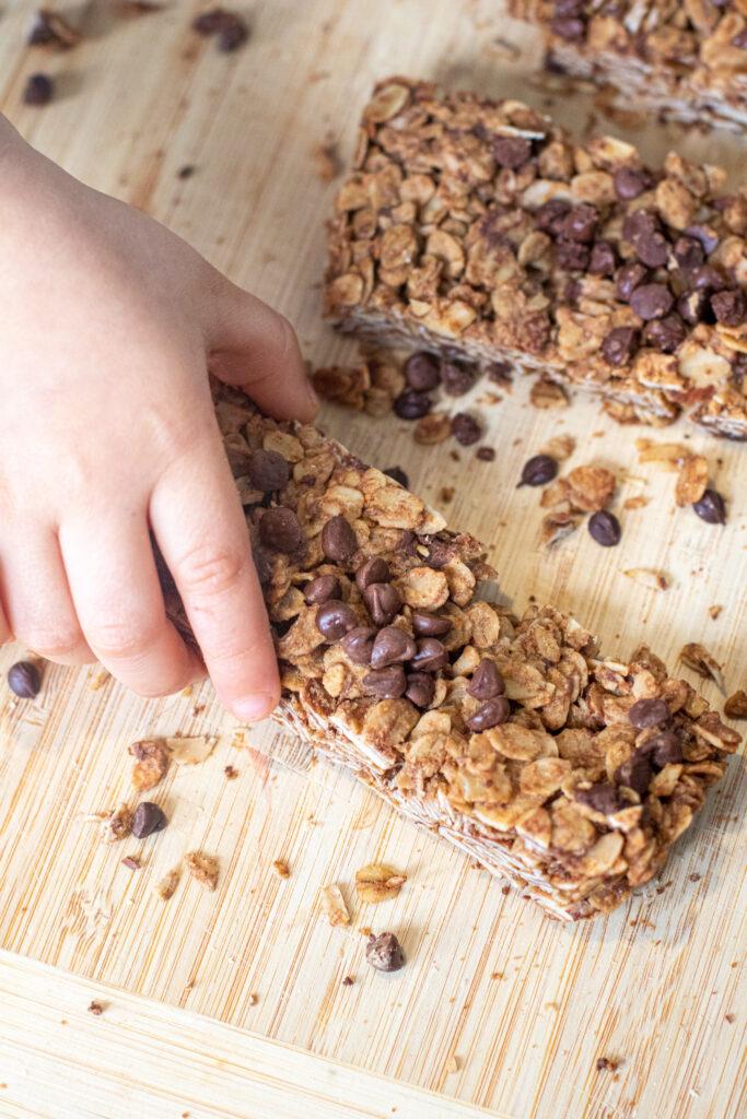 a toddler hand grabbing a granola bar.