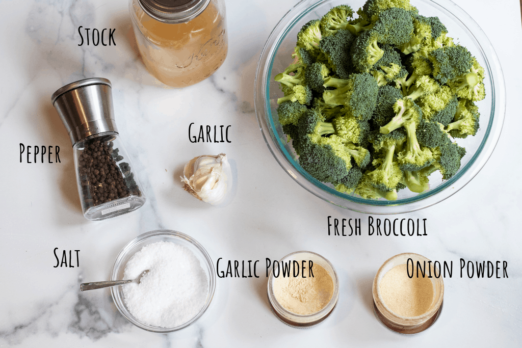 fresh broccoli, stock, pepper, salt, onion and garlic powder, and fresh garlic on a counter.
