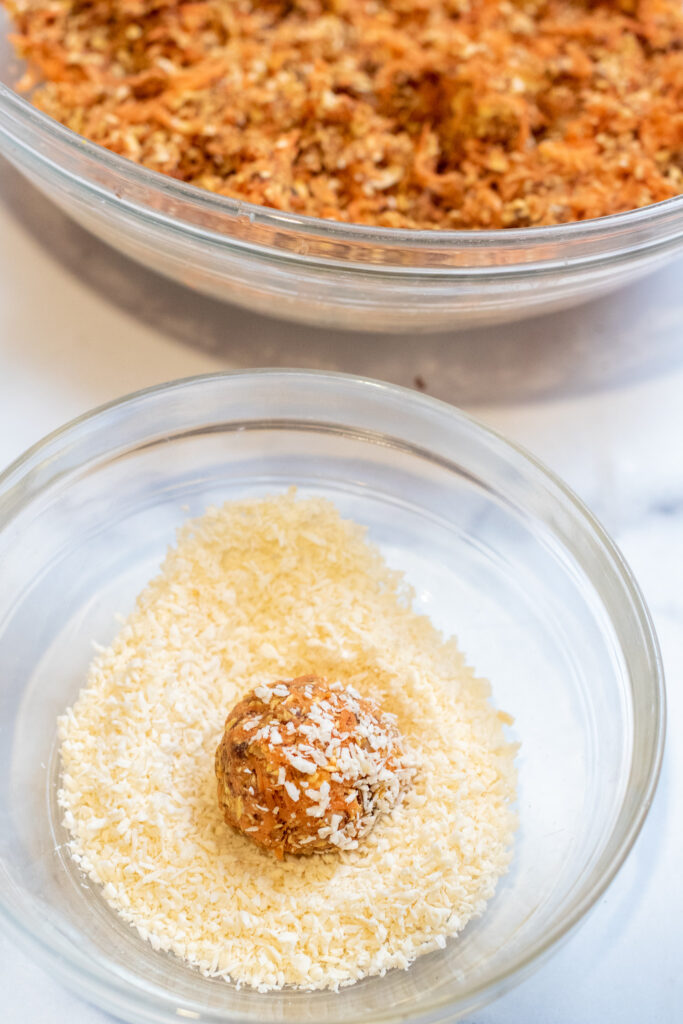 an oat and carrot ball in a bowl of shredded coconut.