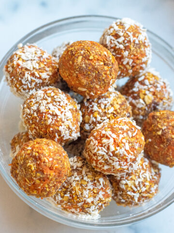 a bowl of balls of oats and carrots with some coated with coconut and some not.