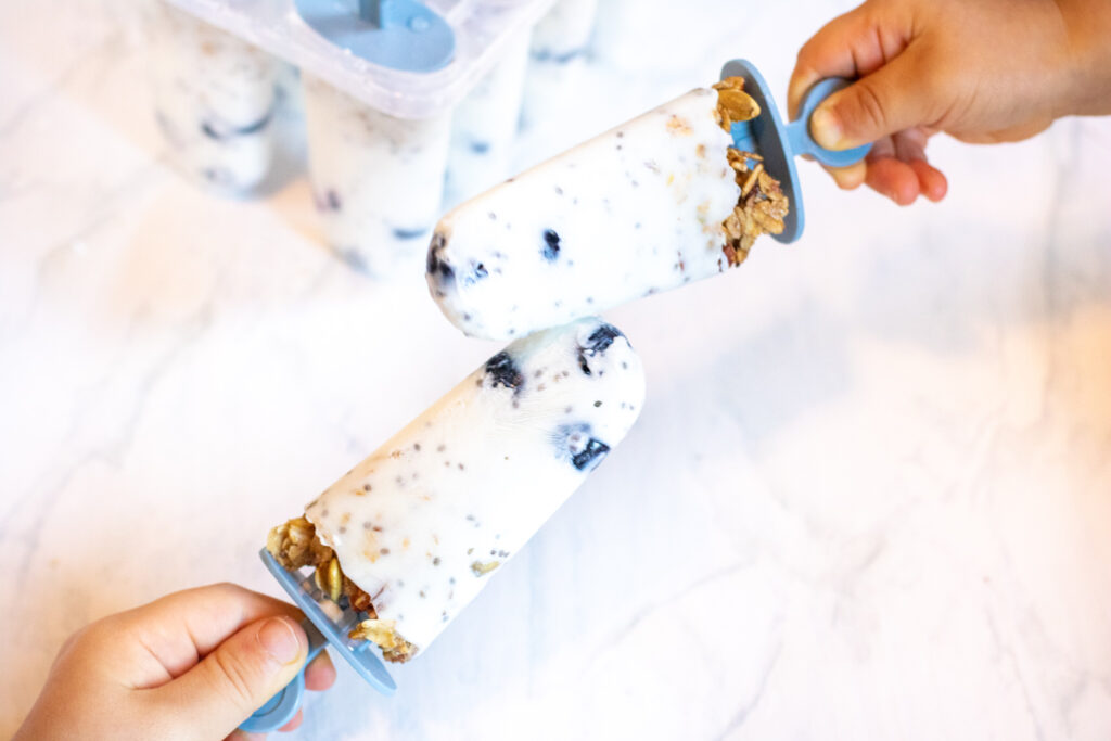 two kids holding yogurt popsicles touching.