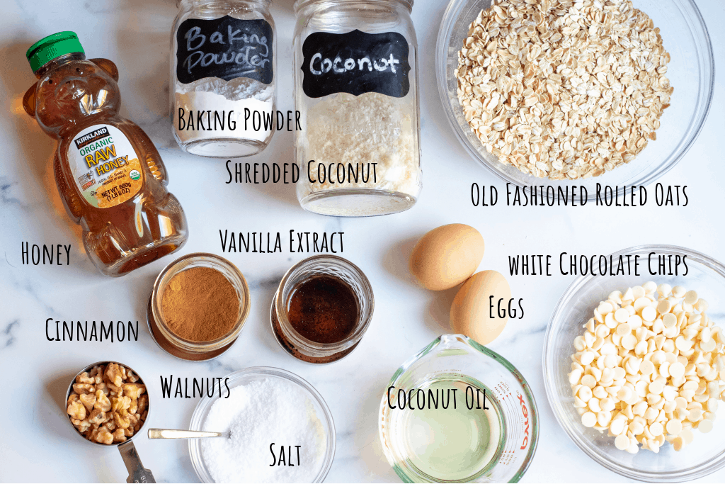 oats, coconut, baking powder, honey, cinnamon, vanilla, eggs, melted coconut oil, walnuts, salt, white chocolate chips on counter.