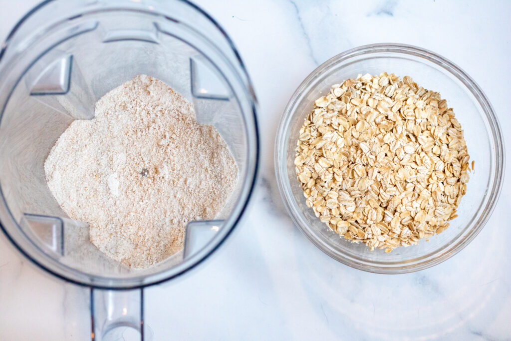 a blender with oat flour and a bowl of oats.