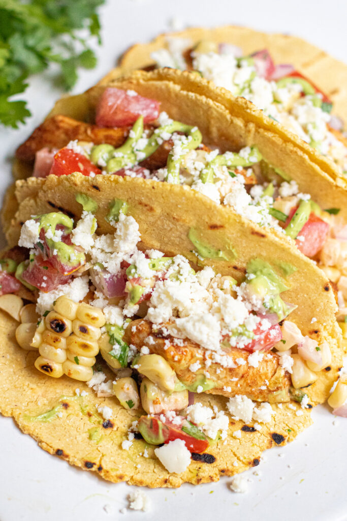 a plate of 3 corn tortilla tacos topped with crumbled cotija cheese.