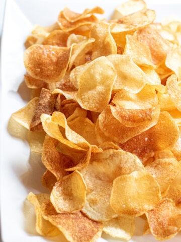 a plate of thin crispy potato chips.