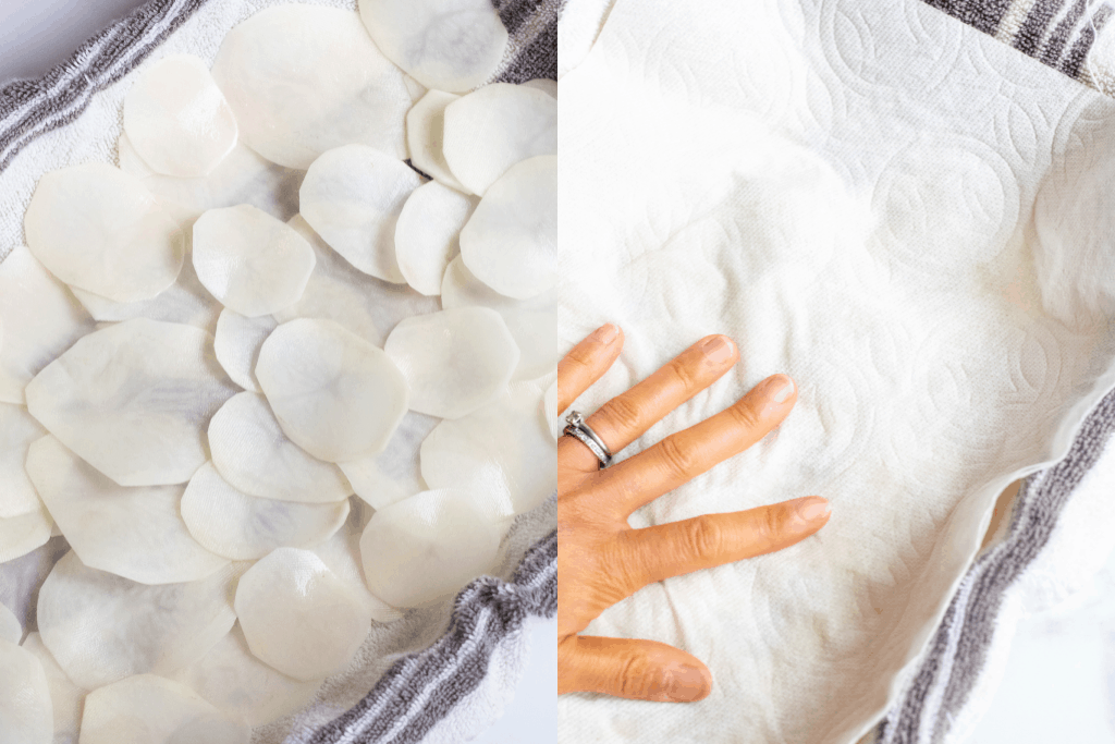 sliced potatoes on a towel and a hand holding a paper towel down.