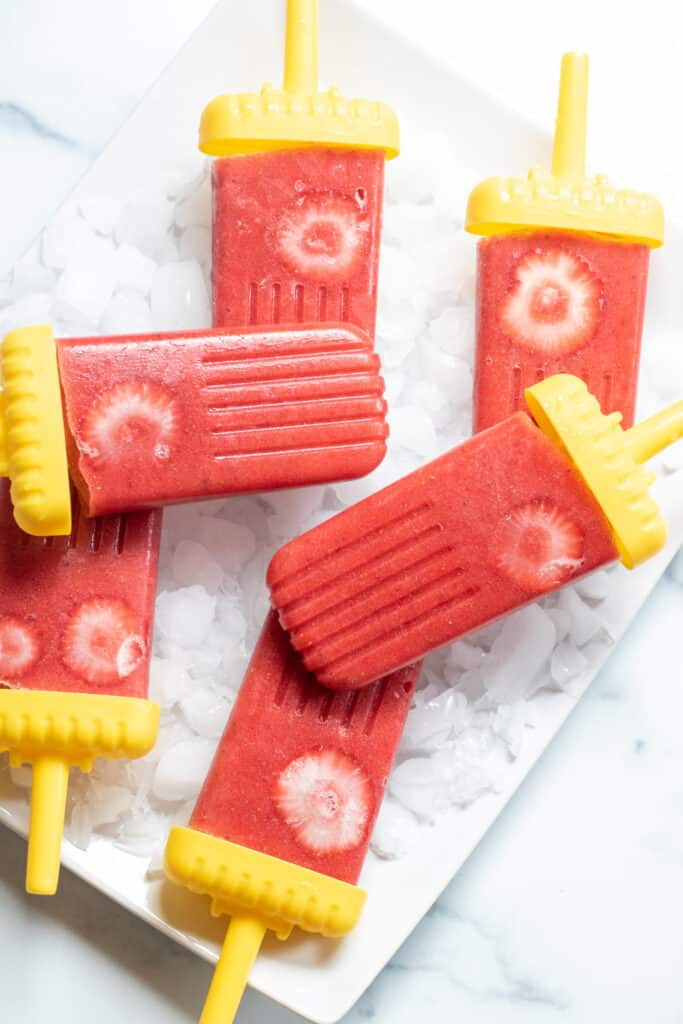 strawberry popsicles on a plate.