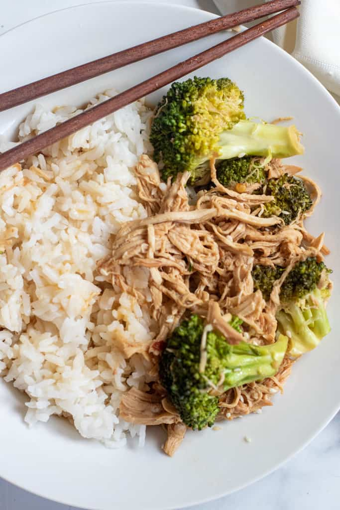 a plate with chopsticks, rice, and shredded chicken and broccoli.