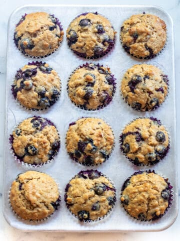a muffin tin of blueberry muffins.
