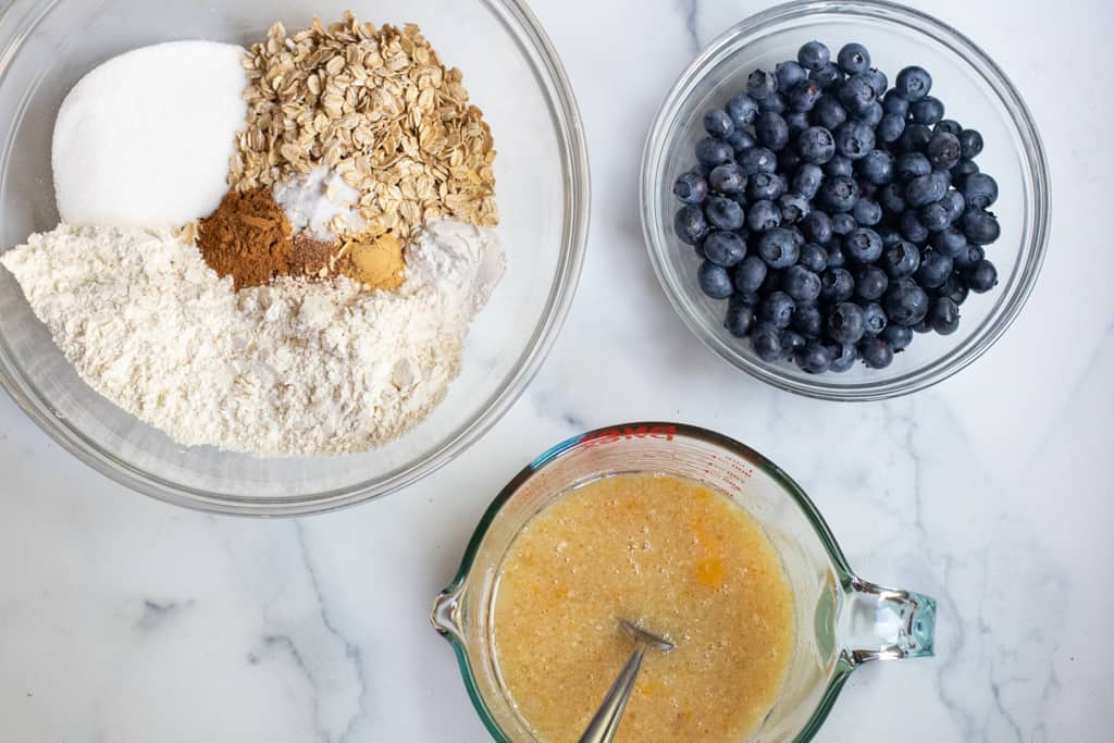 a bowl of oats, flour, sugar, spices, blueberries, and a pyrek of eggs and oil.