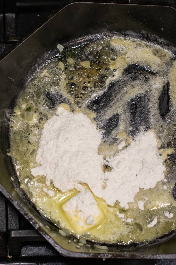 a roux being made in a cast iron skillet.