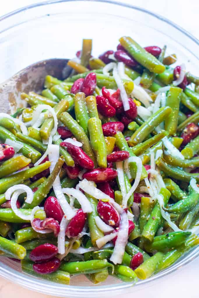 a large bowl with wooden spoon and bean and onion salad.