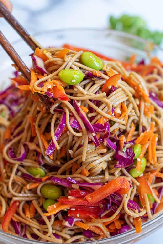 chopsticks holding up a soba noodle salad.