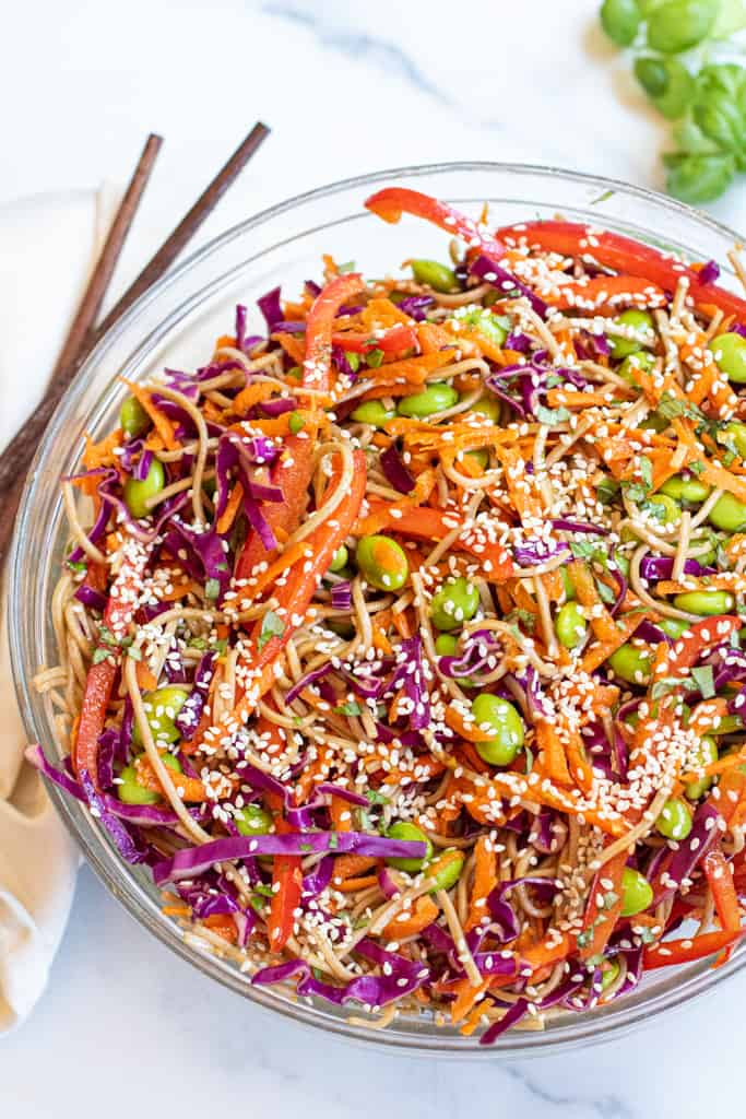 a bowl of soba noodles with cabbage, carrots, edamame, and sesame seeds.