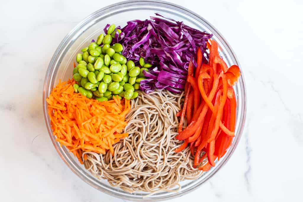soba noodles, carrots, sliced red pepper, cabbage, and edamame in a bowl.