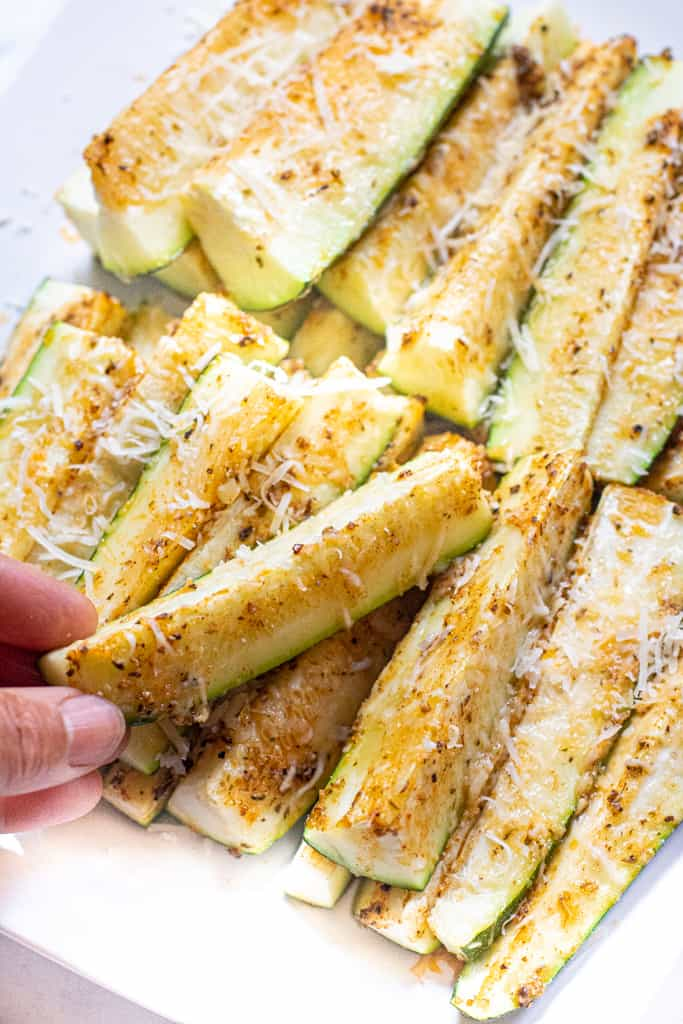 a hand grabbing a zucchini spear from a plate of baked zucchini spears.