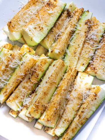 a plate of baked zucchini fries with cheese.