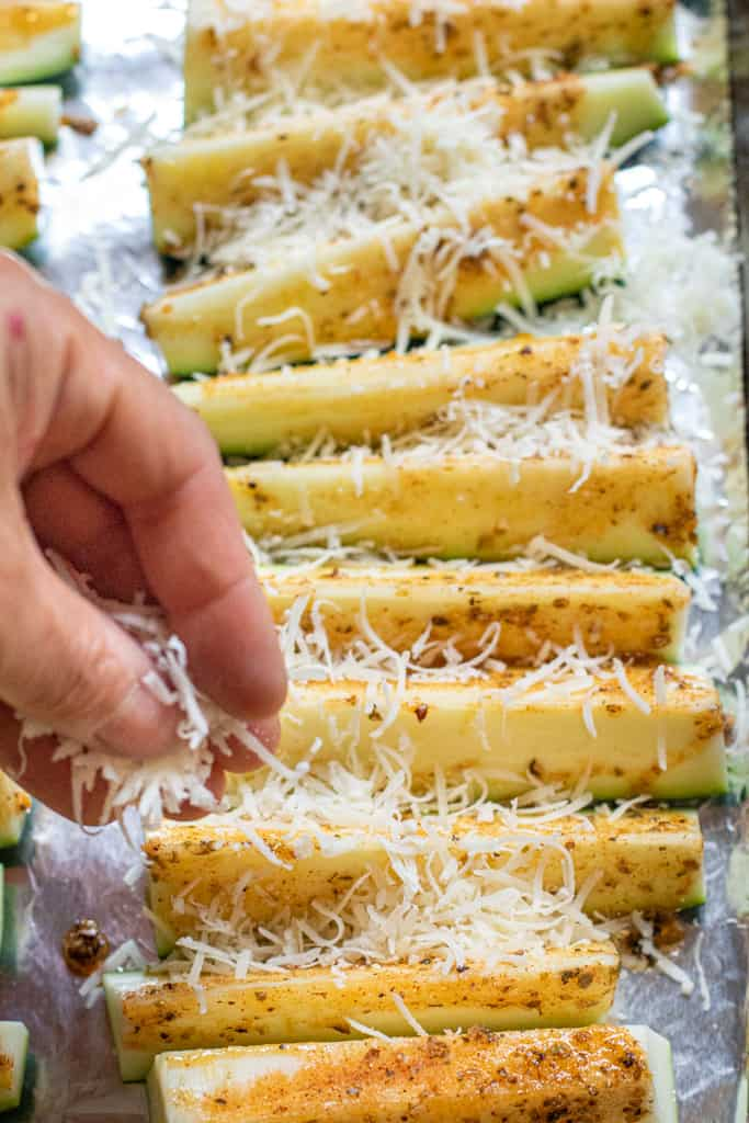 zucchini spears on aluminon foil with a hand sprinkling cheese on them.