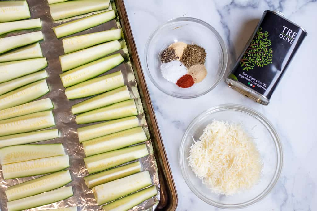 zucchini spears on a baking sheet next to bowl of herbs, cheese, and oil.