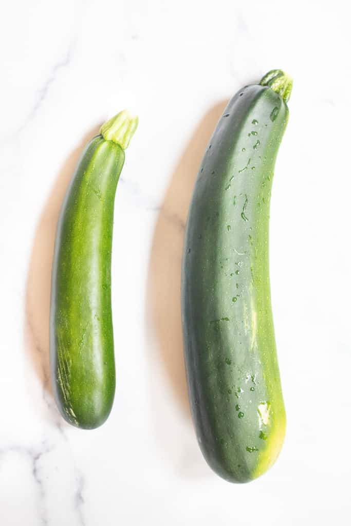 two zucchinis side by side, one regular and one large.