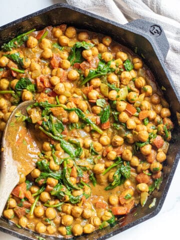 a cast iron of chickpea curry with spinach with a wooden spoon.