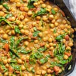 a cast iron of chickpea curry with spinach.