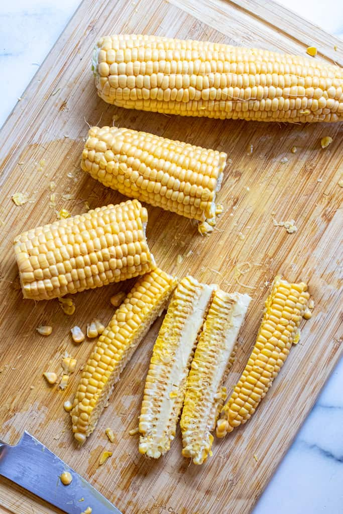 a whole ear of corn, two halves, and then one half quartered on a cutting board.