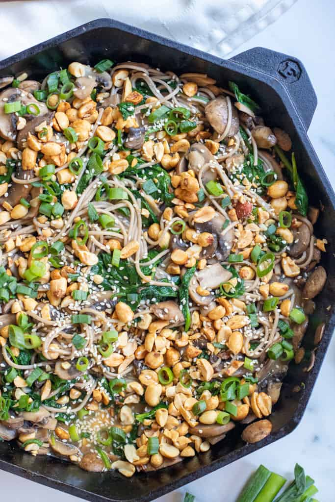 cast iron of noodles with spinach, mushrooms, topped with peanuts and scallions.